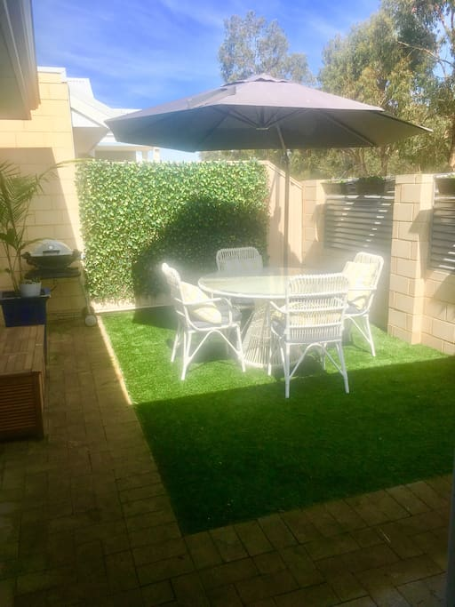 Side courtyard - great for enjoying your breakfast, morning coffee, reading a great book or enjoying the sun! Umbrella for shade, adjustable louvres for light / privacy, and gate for side access.  Direct access to dining/lounge area from this courtyard.