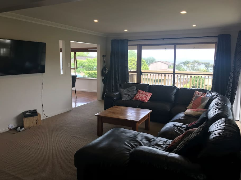 Lounge with large comfy couch for the whole family. PlayStation, Netflix and Lightbox. Leads out to deck with view