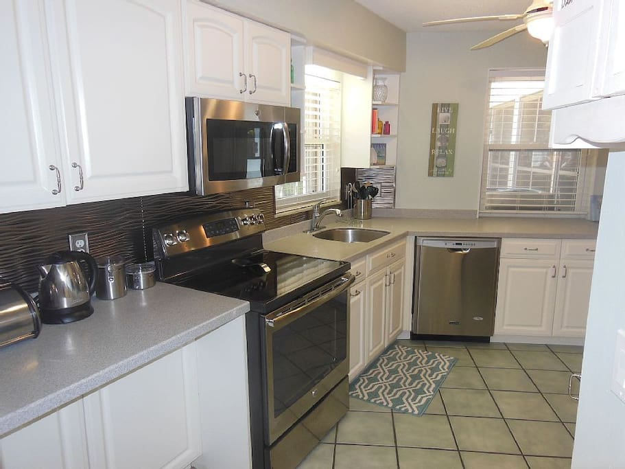Well equipped kitchen with stainless steel appliances and Corian counters