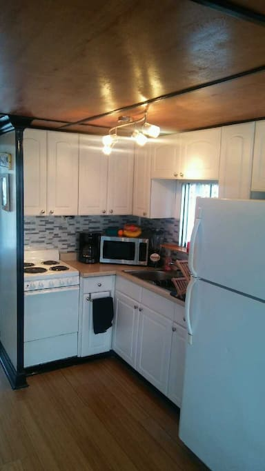 Complete kitchen with a fullsize refrigerater, 4 burner stove, oven, microwave and duel sink.
