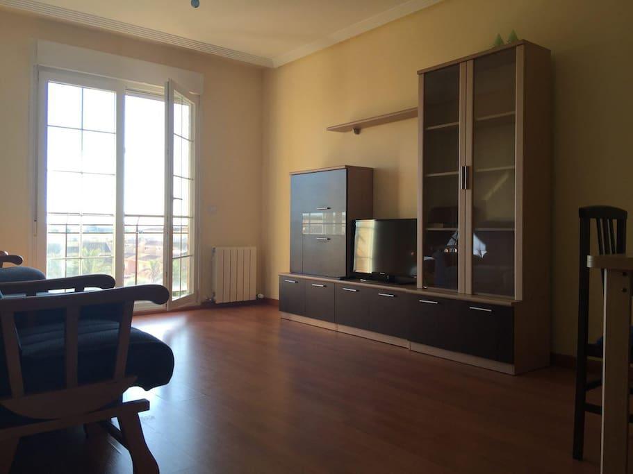 En el salón hay TV, sofá, mesa de trabajo...