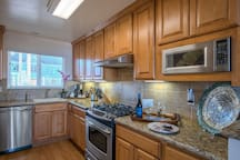 Beautiful fully equipped kitchen with stainless appliances and granite countertops.