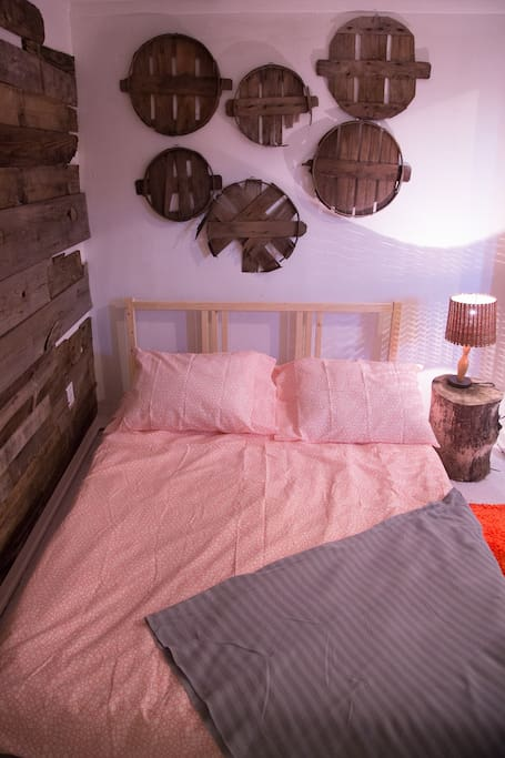 Headboard wall decorated with a collection of vintage rustic apple bin lids.