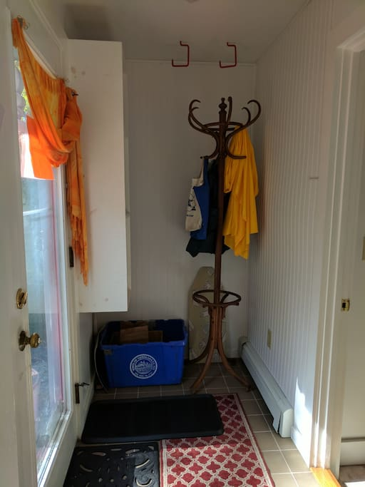 Entryway/Mudroom in Studio looking left upon entry. Front door visible on left along with coat rack, recycle bin and boot/shoe storage section. Bicycle hooks visible overhead.
