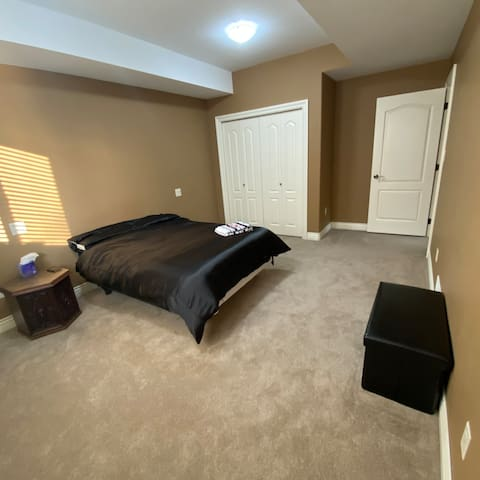 Large second bedroom with double bed and closet. Black ottoman for suitcases or to sit on. Single mattress also available to go on the floor if requested.