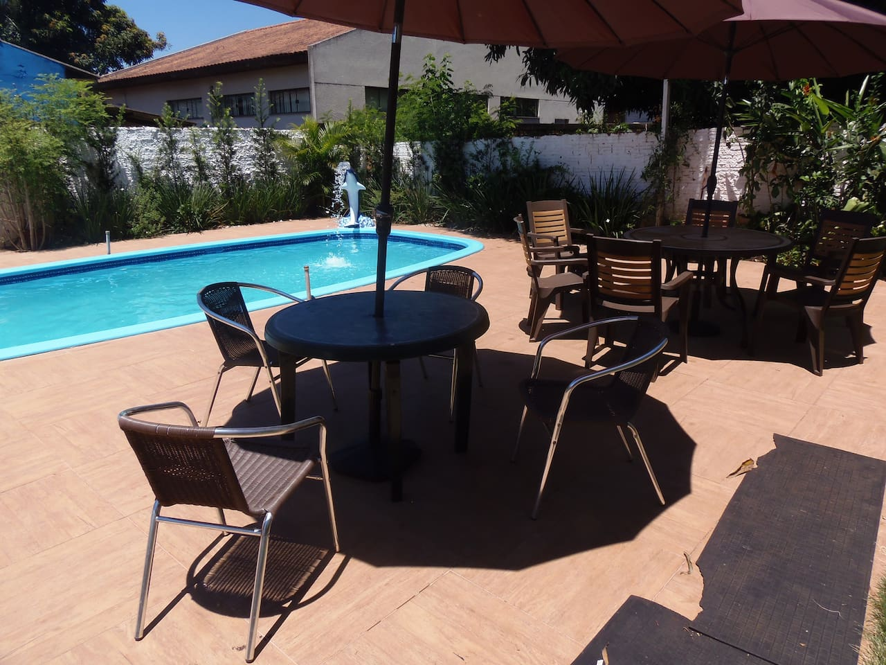 Our beautiful on a sunny day! The pool with the outdoor tables, sun umbrellas and the power Dolphin!