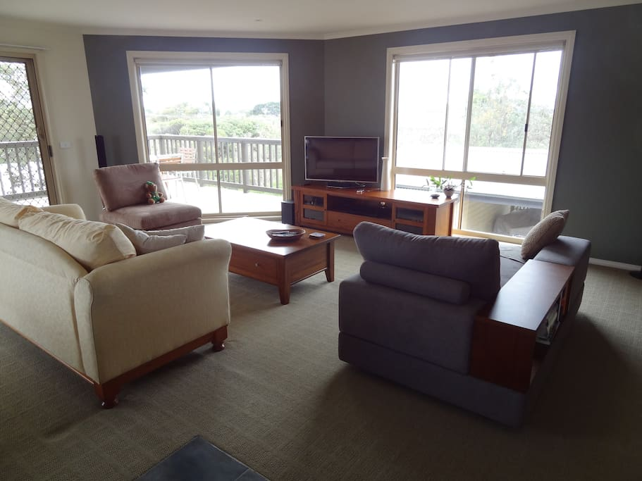 Bright open upstairs living area with views to the inlet.