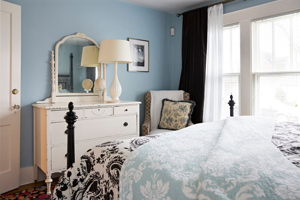 Antique dresser with large mirror in king bedroom
