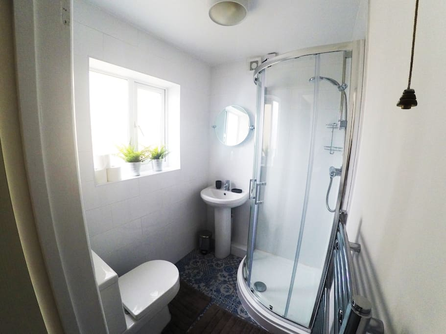 Practical shower room with heated towel rail.