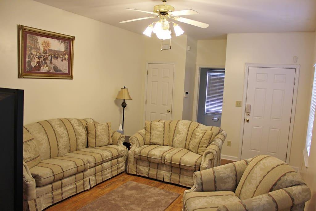 Living Room with Queen Sleep Sofa Front Door Half Bath Door Open and Coat Closet