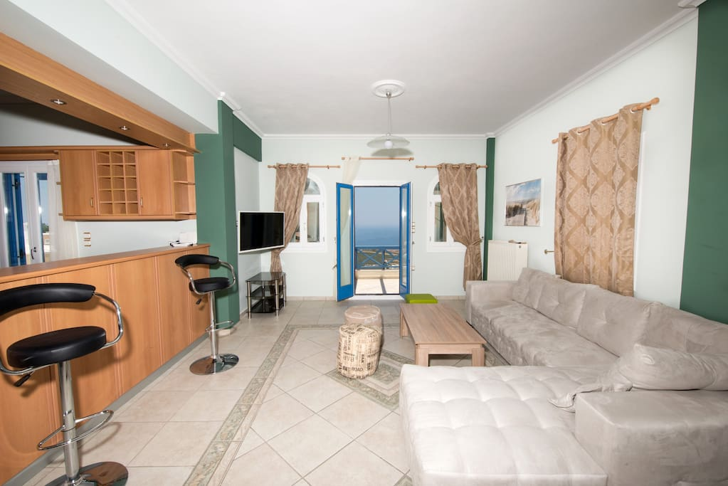 Airconditioned living room with a balcony and satelite Tv..