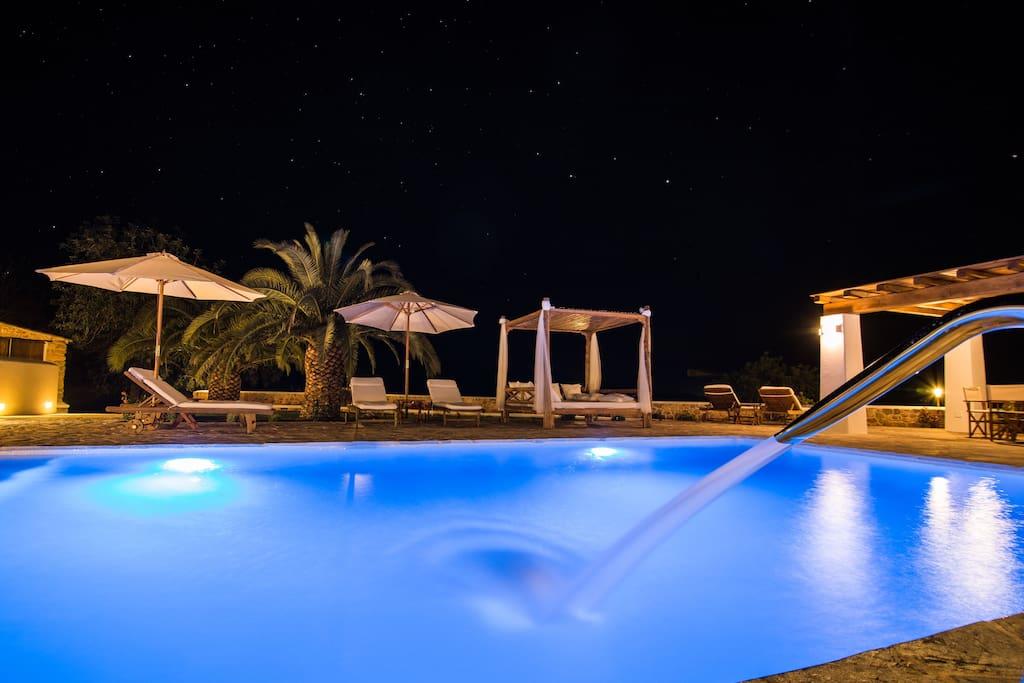 Vista de las tumbonas y la cama balinesa por la noche