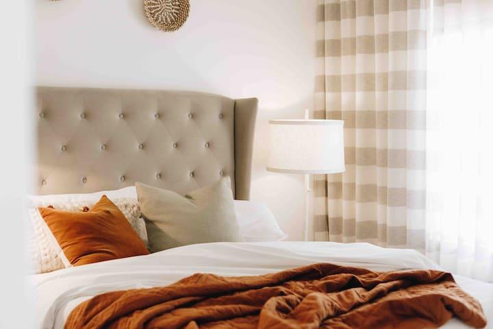 Luxurious bedding, crisp white linens and a premium pillow topper mattress for a restful and serene sleep.