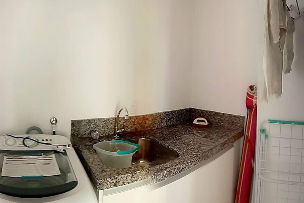 Área de serviço com tanque, varal e maquina de lavar roupas.