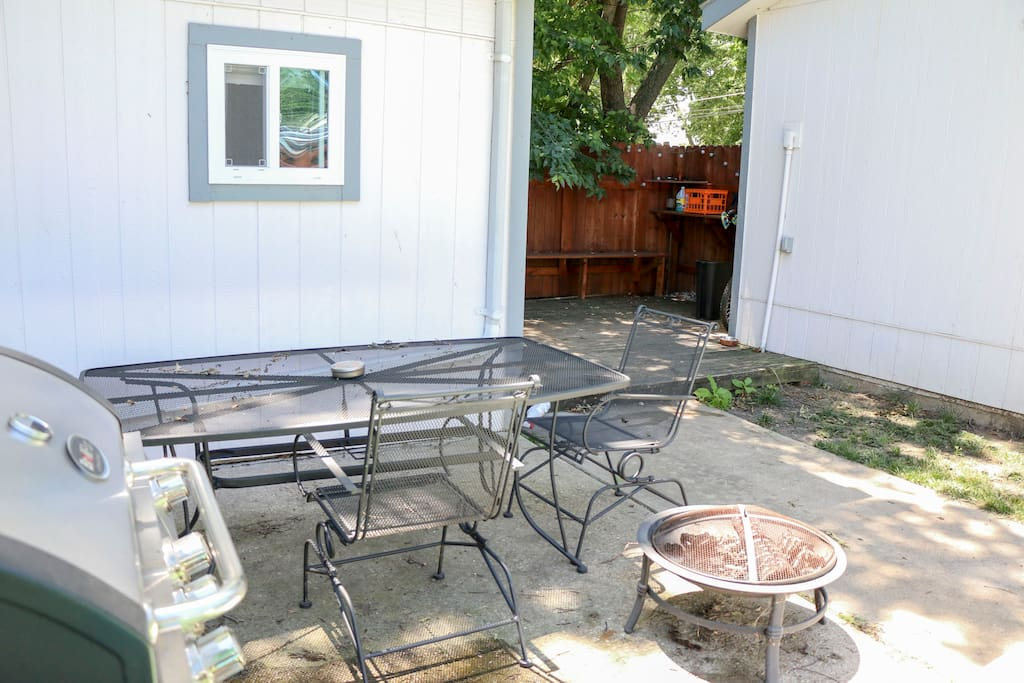 Private, fenced backyard with table and chairs along with a gas grill.