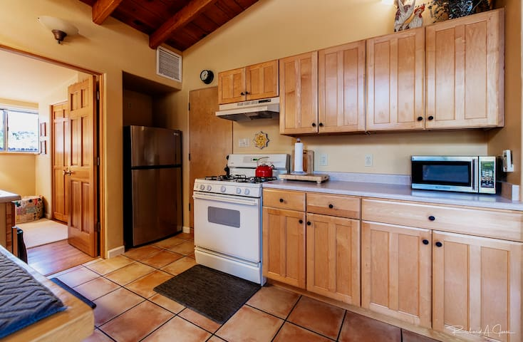 Full Kitchen with range, microwave and refrigerator.
