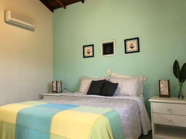 Suíte verde no andar superior, com varanda, ar condicionado tipo split e cama Queen size.
