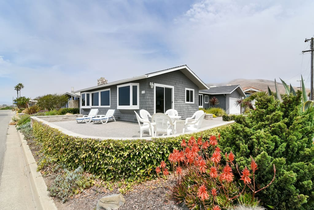 A large front patio with lounge furniture and patio seating is perfect for enjoying this beach front home
