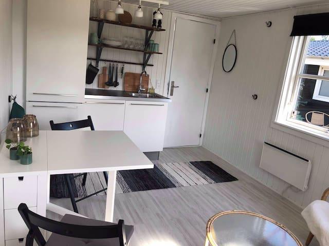 Køkken og spisebord, hvor der er plads til fire omkring når det er slået ud.