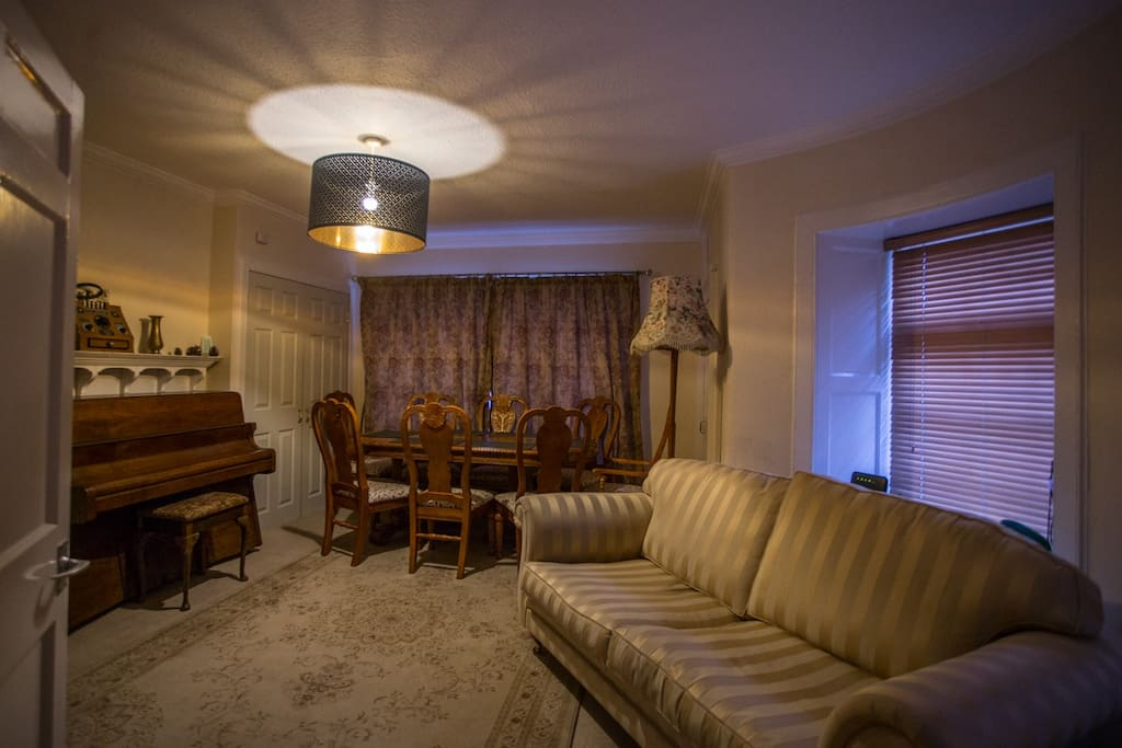 A comfortable dining room with an 8-seater table. In this picture it is shrunk to 6. There's also a tuned and playable real piano.