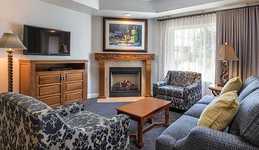 This living room includes queen pullout sofa + chairs, TV, fireplace, and access to your private balcony.