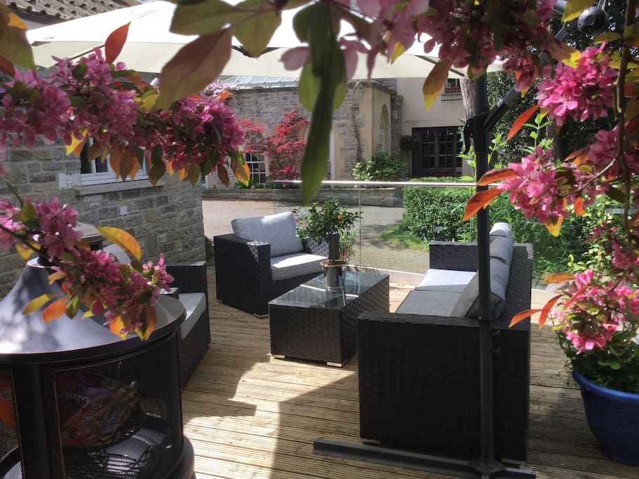 Lovely outside space with wooden decking a barbecue and comfortable garden furniture