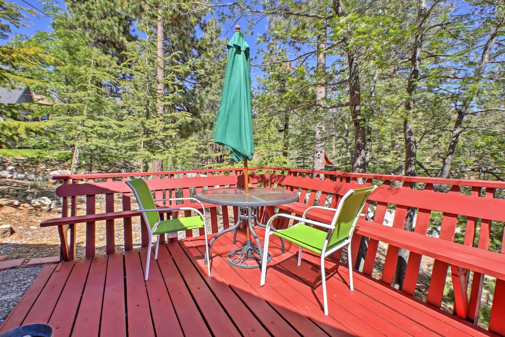 This charming property boasts a spacious deck with an abundance of outdoor furniture and tranquil forest views.