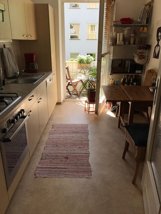 Fully equipped kitchen with access to balcony facing backyard