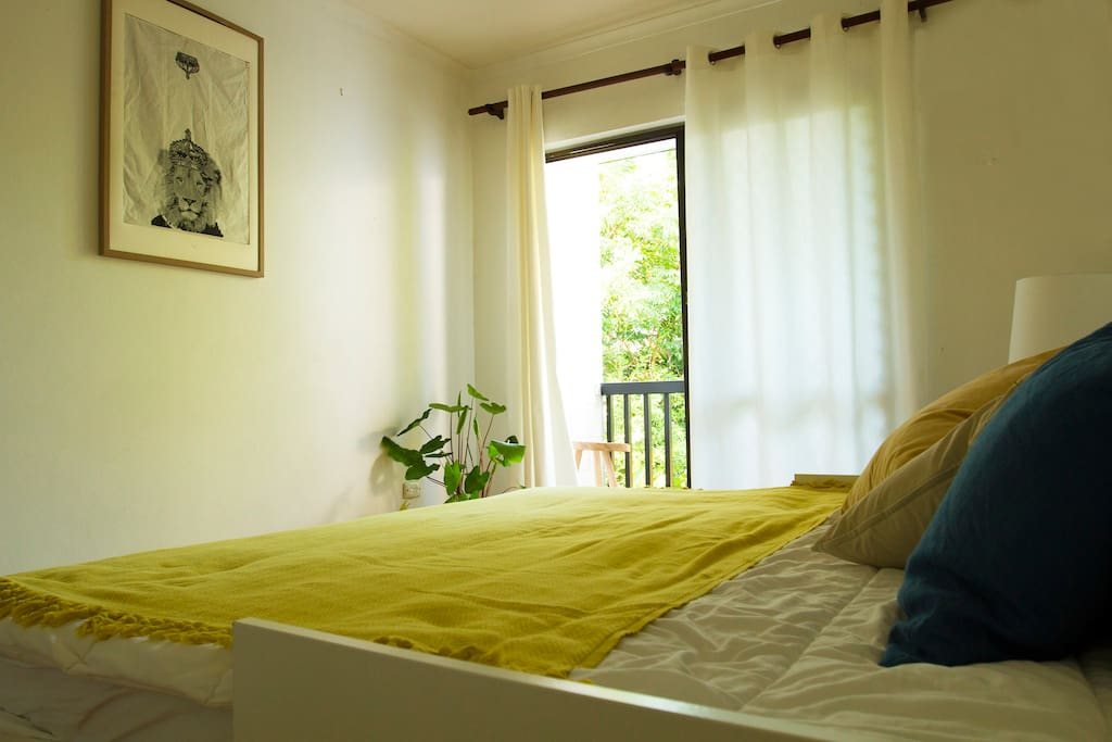Bedroom 2 with balcony overlooking tropical garden
