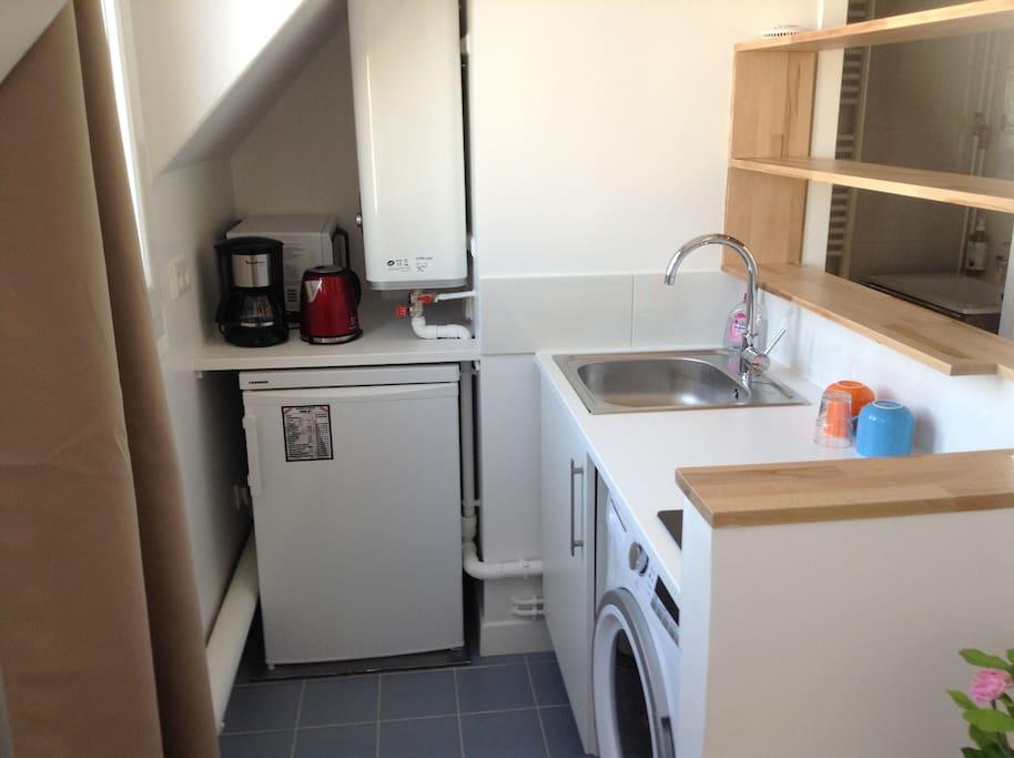 Frigidaire, bouilloire, machine à café, micro-ondes, évier, placards, l'essentiel d'une cuisine