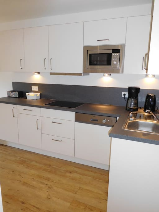 Keuken met vaatwasser, magnetron, filterkoffie, waterkoker, toaster.