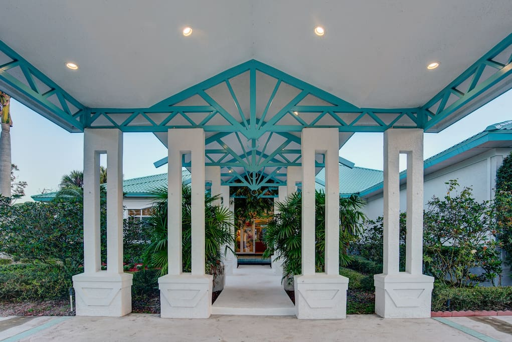 The front of the Tropical Retreat Estate Home has covered parking and a grand entrance.