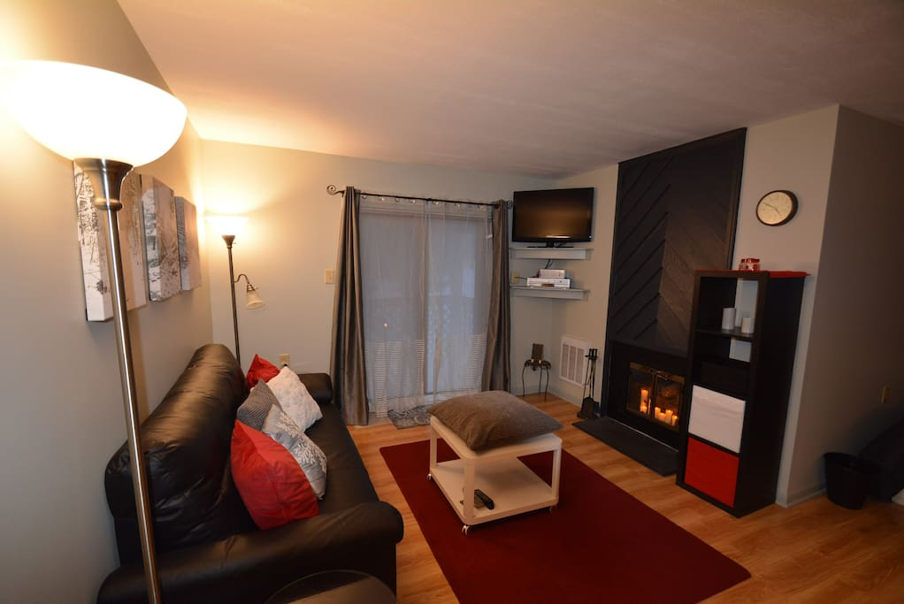 A Roomy Living Room with Candle Fireplace, TV, A Place to Put Your Feet Up