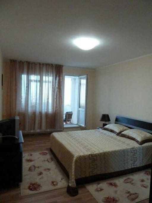 kingsize bedroom with balcony that has a coffee table and chairs