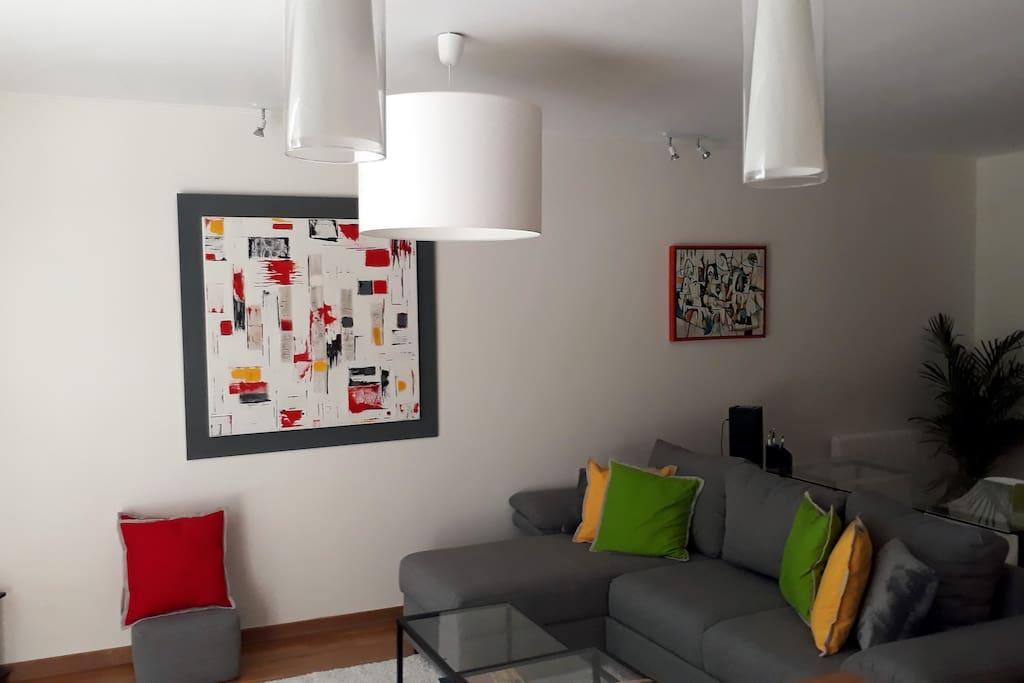 Salon avec grande baie vitrée donnant sur la terasse et le jardin, canapé 4 places + 4 poufs, transformable en un confortable lit de 140cm, TV écran plat, Coin bureau