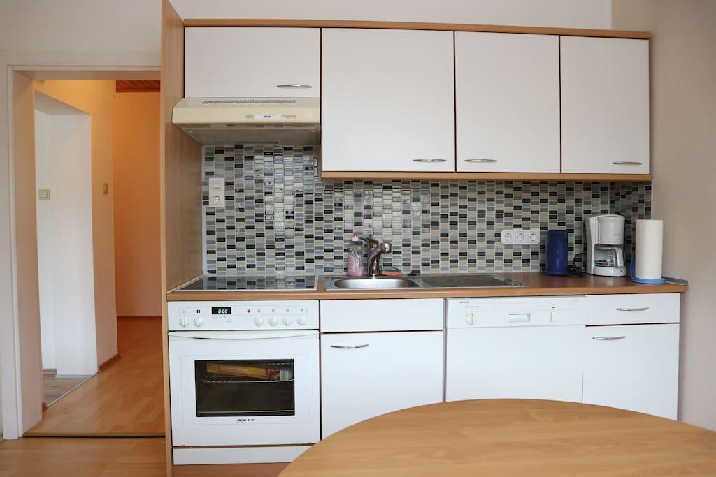 Küche mit Geschirrspüler, E-Herd und Kühlschrank mit Gefrierfach