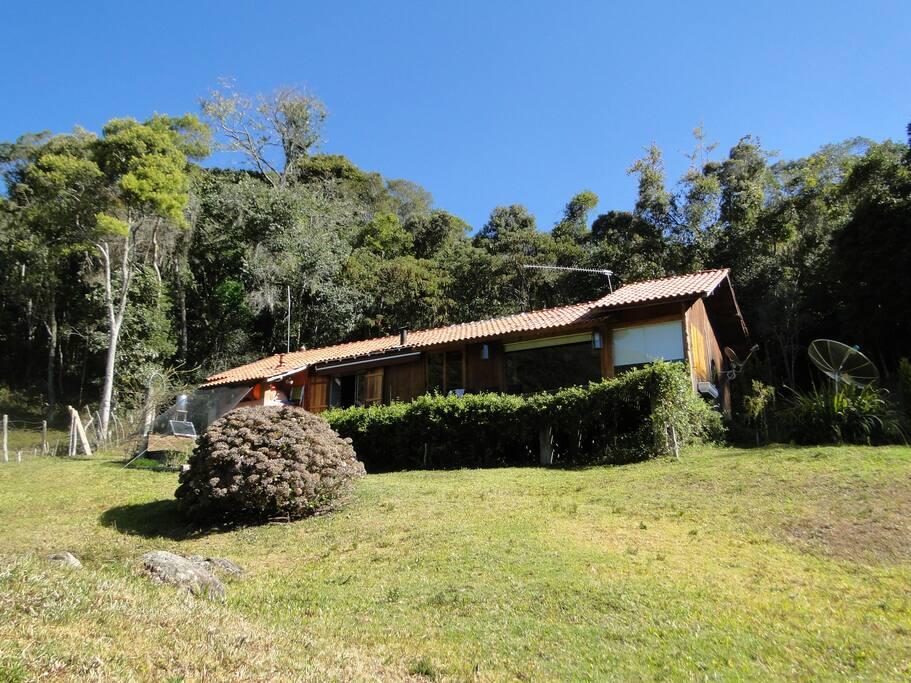 Casa em madeira com amplo deck, sauna a lenha e ducha.