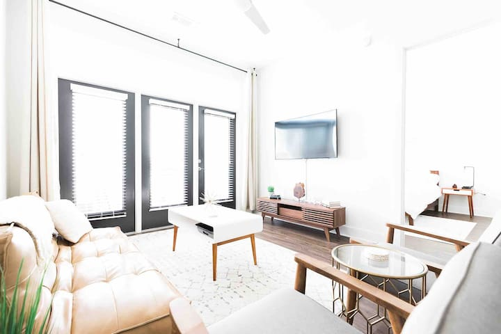 """Living room area with door to balcony and 55"""" curved smart tv."""