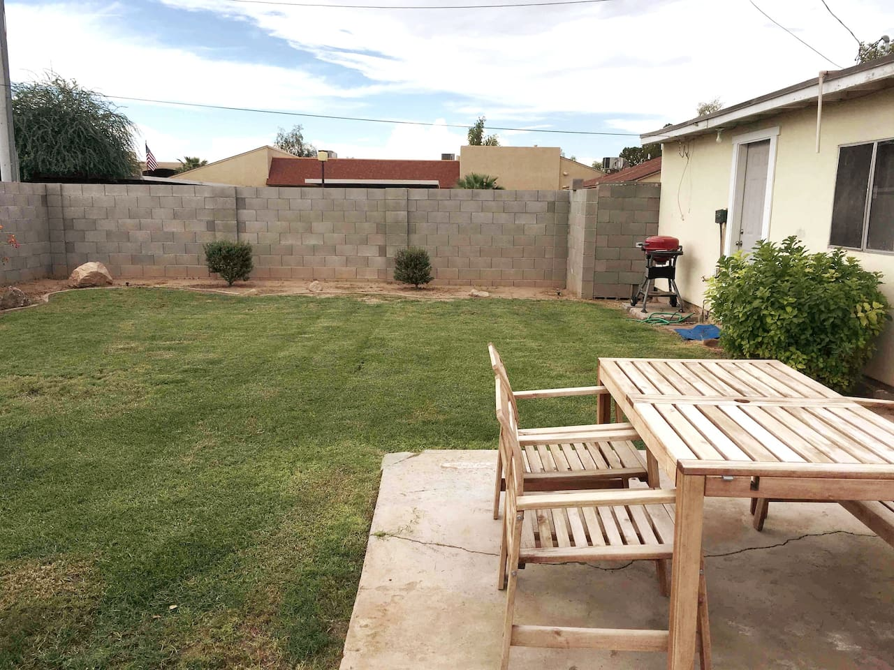 Backyard with lawn, patio table and BBQ grill