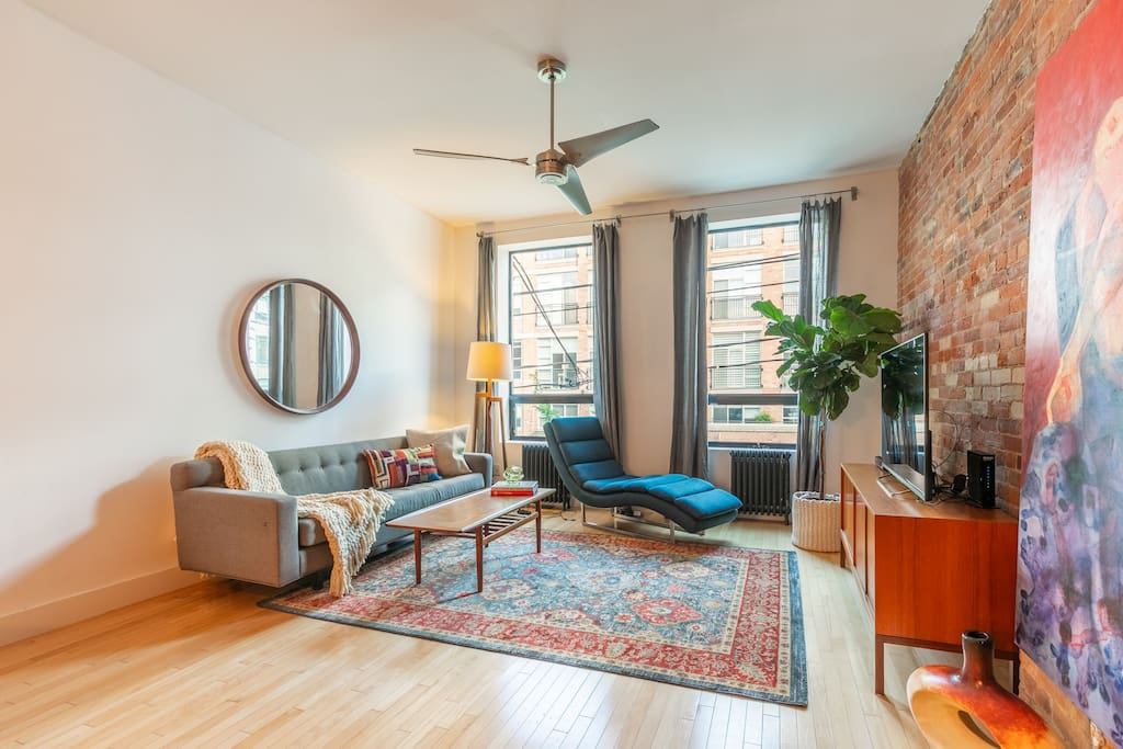 Spacious living room with exposed brick wall, mid-century modern furniture and floor to ceiling windows overlooking Queen West