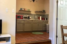 This unit is so warm, cozy and sweet. This is a lovely view from the couch looking at the kitchen. Large opening and beautiful light fixture in the kitchen