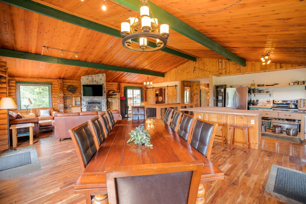 Great room with two sitting areas, dining table that can seat 10, and kitchen.