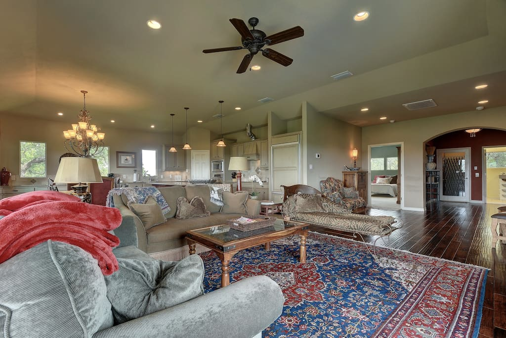 An open and airy living room features elegant seating, dark hardwood floors and a TV.