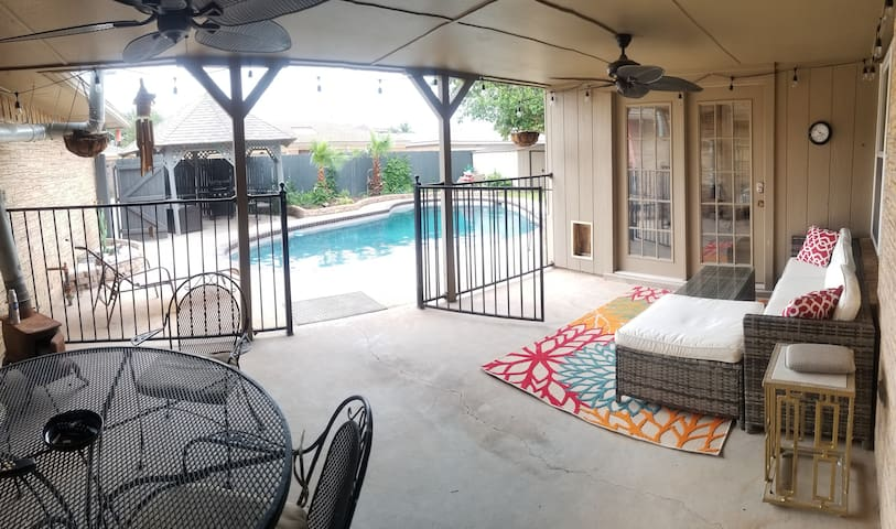 Backyard patio with table,  TV,  and couch .  Private access to office w attached master bedroom