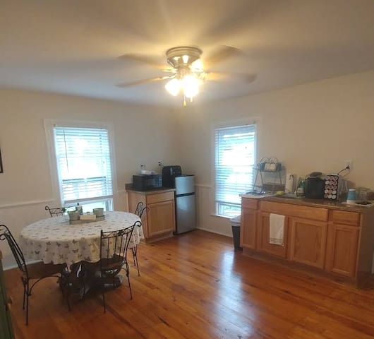 Kitchenette Ceiling Fan AC Mini Fridge Microwave Toaster Keurig with Coffees and Teas Sink Dishes and Silverware Loveseat Table with 4 Chairs