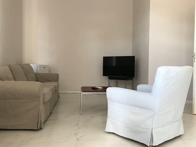 Living room: sofa, sofa chair, coffee table,  tv and cold fridge