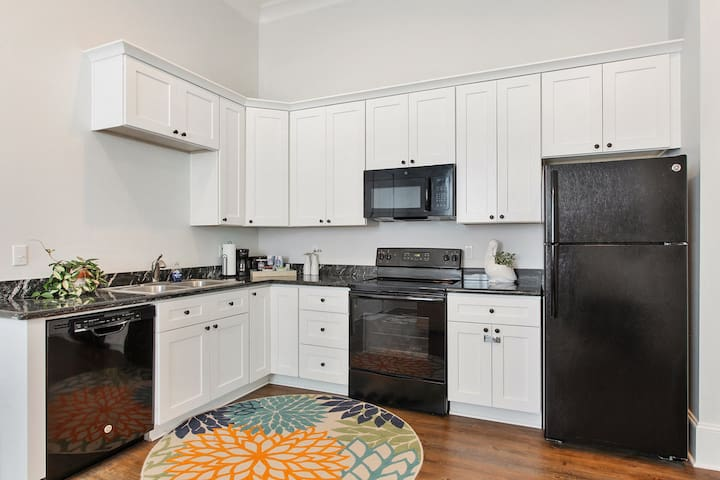 Kitchen is complete with dishwasher, stove, oven, microwave, coffee maker, toaster, and fridge with ice maker.
