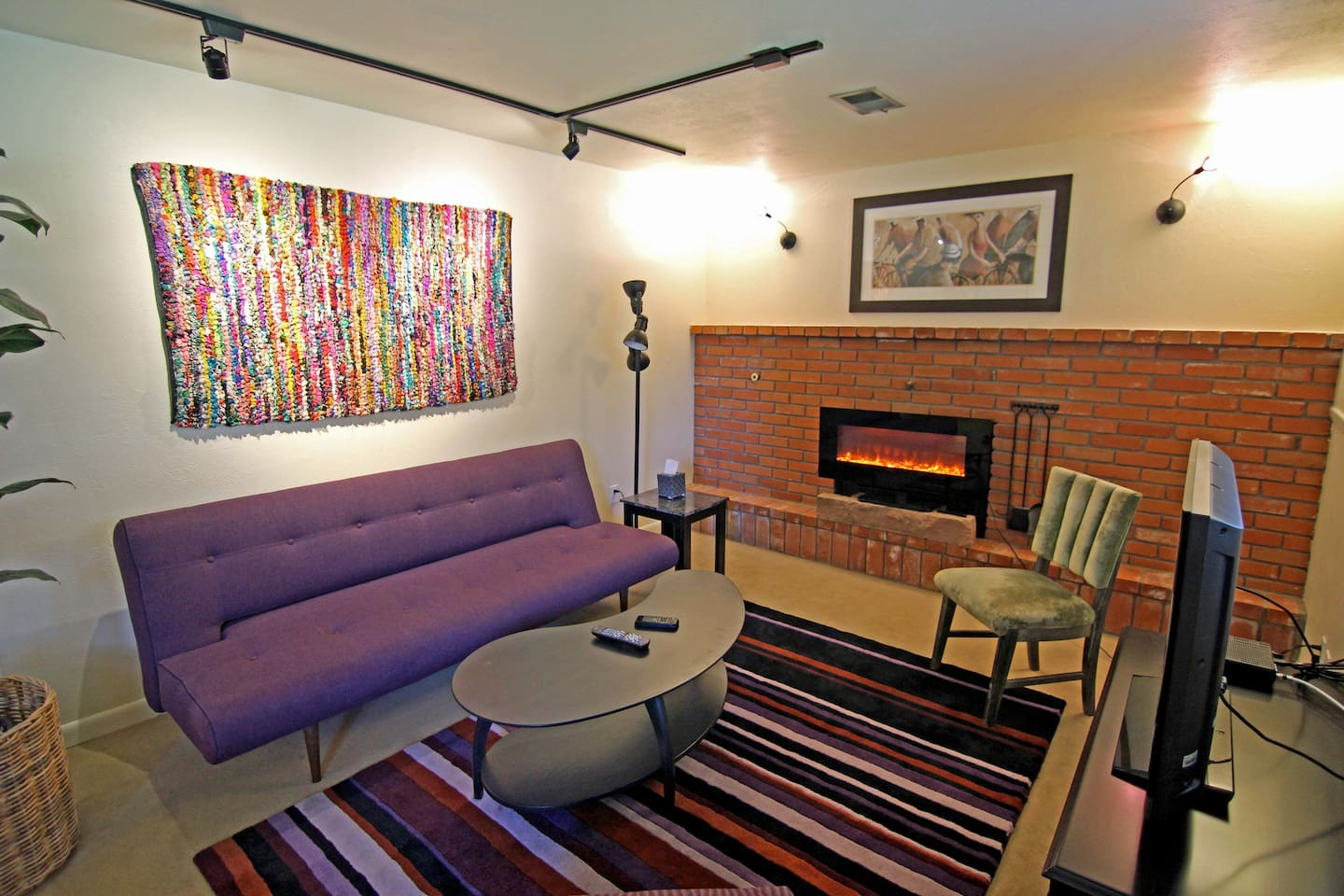 Comfy sitting area with electric fire, satellite TV, and reading lamp. Couch becomes full-size bed.