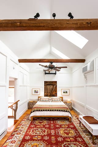 The queen-sized bed and crib space. This photo was taken midday, when the room is considerably brighter. Two large bedside tables, individual (and adjustable) reading lights are easily at hand (and the light won't disturb your sleeping partner. Shh!)