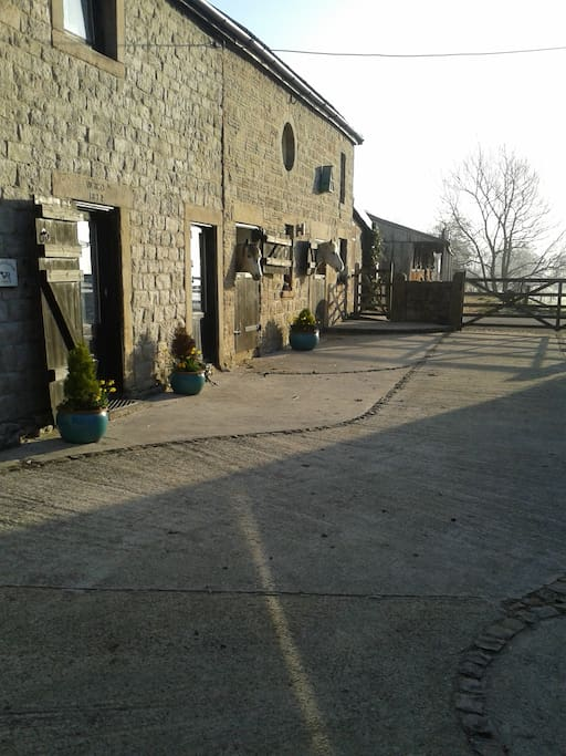 Courtyard with Shippon Cottage on the left and neighbouring working stables